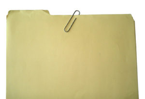 A manila file folder, paper clipped closed